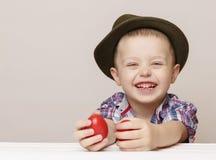 Menino de Laughting 4 anos velho com ovos da páscoa vermelhos Fotografia de Stock Royalty Free