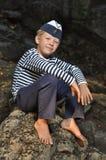 Menino de marinheiro que senta-se em uma pedra Fotos de Stock Royalty Free