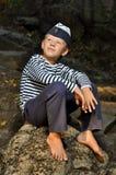 Menino de marinheiro que senta-se em uma pedra Imagens de Stock Royalty Free