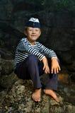 Menino de marinheiro que senta-se em uma pedra Fotografia de Stock