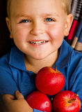 Menino de olhos azuis com maçãs Fotografia de Stock