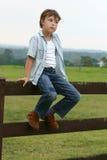 Menino de país que senta-se em uma cerca imagem de stock royalty free