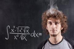 Menino de pensamento que resolve a equação com cabeça de fumo Foto de Stock