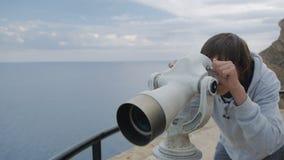 Menino de quinze anos no hoodie cinzento que olha o mar no telescópio da plataforma de observação elevado alta vídeos de arquivo