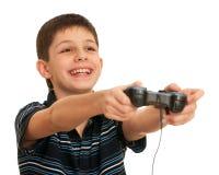 Menino de riso que joga um jogo de computador com manche Foto de Stock