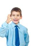 Menino de riso que mostra o gesto aprovado do sinal Fotografia de Stock Royalty Free