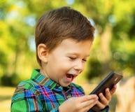 Menino de riso que usa o smartphone Imagem de Stock Royalty Free