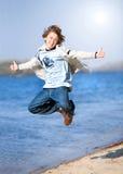 Menino de salto feliz na praia Imagem de Stock