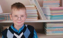 Menino de sete anos cansado com os vidros que sentam-se no assoalho entre os livros Fotografia de Stock Royalty Free