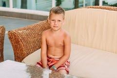 Menino de sete anos em banhar o short em férias no hotel no verão fotografia de stock