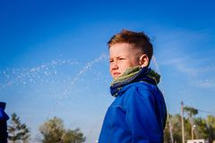 Menino de sete anos em um lenço contra o céu azul fotos de stock