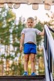 Menino de sete anos na altura completa em um t-shirt branco e short azul em olhares borrados de um fundo natural na câmera no imagens de stock royalty free
