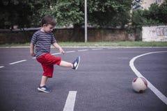 Menino de Smal que joga o futebol no recreio Imagens de Stock