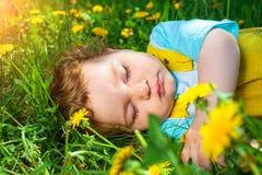 Menino de sono na grama Fotografia de Stock Royalty Free