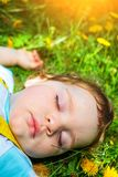 Menino de sono na grama Fotografia de Stock