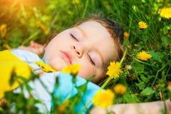 Menino de sono na grama Imagens de Stock Royalty Free
