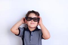 Menino de sorriso bonito feliz nos óculos de sol, tiro do estúdio no branco C imagem de stock