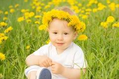 Menino de sorriso bonito no campo da grinalda do dente-de-leão na primavera Fotografia de Stock Royalty Free