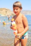 Menino de sorriso bonito que joga com a arma de água na praia durante um dia de verão ensolarado do waarm fotos de stock