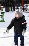 Menino de sorriso bonito que joga com neve foto de stock royalty free