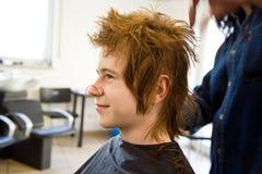 Menino de sorriso com cabelo vermelho no cabeleireiro Foto de Stock