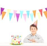Menino de sorriso com chapéu do partido e um bolo de aniversário Fotografia de Stock