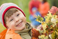 Menino de sorriso com folhas de outono fotos de stock