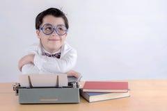 Menino de sorriso com máquina de escrever foto de stock