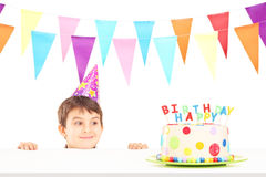 Menino de sorriso com o chapéu do partido que olha um bolo de aniversário Fotografia de Stock Royalty Free