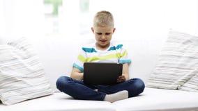 Menino de sorriso com o computador do PC da tabuleta em casa vídeos de arquivo