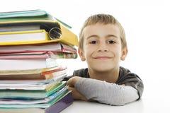 Menino de sorriso com os livros de escola na tabela Fotos de Stock