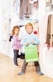 Menino de sorriso com saco de compras e menina atrás Imagens de Stock