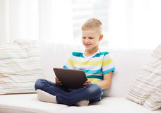Menino de sorriso com tablet pc em casa Foto de Stock