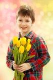 Menino de sorriso com um ramalhete de flores amarelas Imagem de Stock