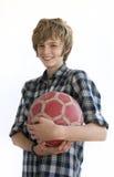 Menino de sorriso com uma esfera de futebol velha Foto de Stock