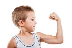 Menino de sorriso da criança do esporte que mostra a força de músculos do bíceps da mão imagens de stock