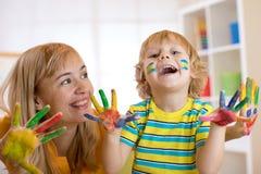 Menino de sorriso da criança e sua mãe que têm o divertimento e que mostram as mãos pintadas em pinturas coloridas Imagem de Stock Royalty Free