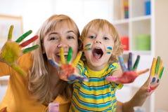 Menino de sorriso da criança e sua mãe que têm o divertimento e que mostram as mãos pintadas em pinturas coloridas Imagem de Stock