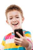 Menino de sorriso da criança que mantém o telefone celular ou o smartphone que tomam o auto Fotografia de Stock Royalty Free
