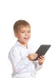 Menino de sorriso da leitura com livro eletrônico. Isolado Foto de Stock Royalty Free