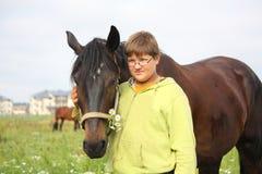 Menino de sorriso do adolescente com os cavalos no campo Fotos de Stock Royalty Free