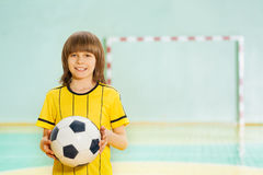 Menino de sorriso do preteen que guarda a bola de futebol nas mãos Fotos de Stock