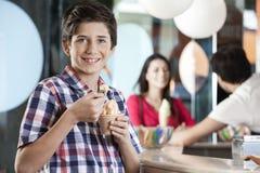 Menino de sorriso do Preteen que tem o gelado na sala de estar Fotos de Stock Royalty Free