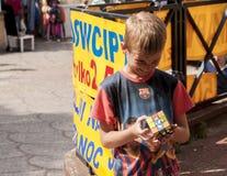 Menino de sorriso do yung que tenta resolver o cubo de um Rubik da inteligência Fotografia de Stock