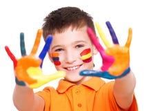 Menino de sorriso feliz com mãos e cara pintadas Fotografia de Stock