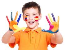 Menino de sorriso feliz com mãos e cara pintadas Imagem de Stock Royalty Free
