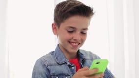 Menino de sorriso feliz com smartphone em casa video estoque