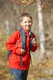 Menino de sorriso feliz do caminhante com trouxa Foto de Stock
