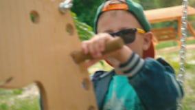 Menino de sorriso feliz em um balanço de madeira sob a forma de um cavalo em um parque na luz solar Uma criança nos óculos de sol video estoque