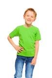 Menino de sorriso feliz no t-shirt e na sarja de Nimes verdes Fotografia de Stock